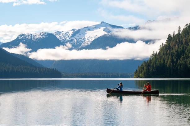 Paar Kanufahren auf See gegen schöne Berg – Foto