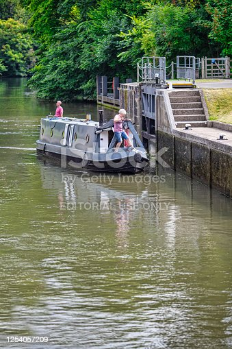 istock Couple carefully navigate their canal narrow boat into a Lock at Cookham, Berkshire. England. 1254057209