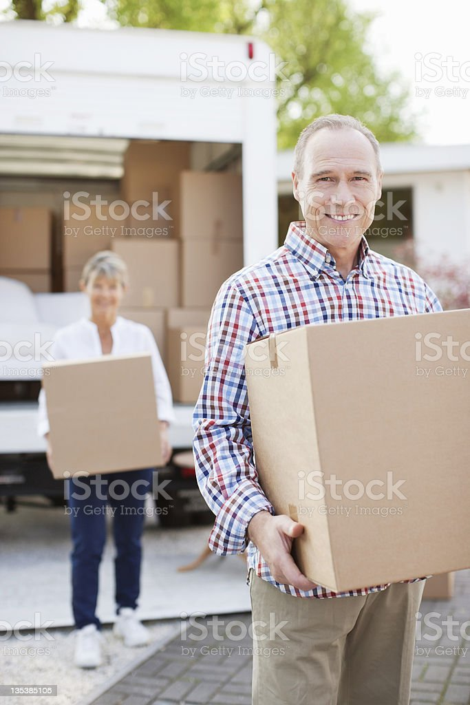Couple carrying boxes from moving van royalty-free stock photo