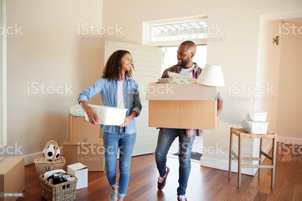 Couple Carrying Boxes Into New Home On Moving Day stock photo