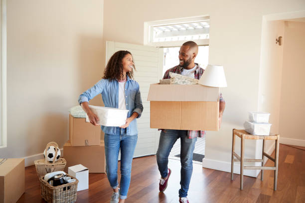 couple carrying boxes into new home on moving day - house hunting stock photos and pictures