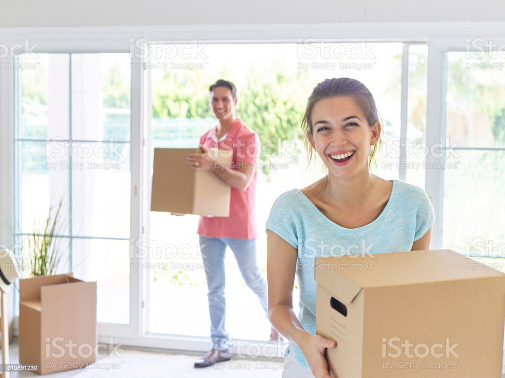 couple carrying cardboard boxes and smiling stock photo download image now istock. Black Bedroom Furniture Sets. Home Design Ideas