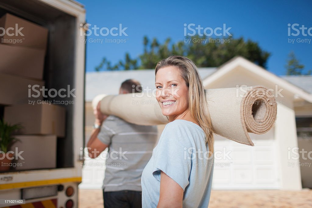 Couple carrying carpet from moving van royalty-free stock photo