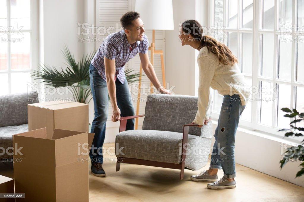 Couple transportant chaise ensemble, en plaçant les meubles se déplaçant dans la nouvelle maison - Photo