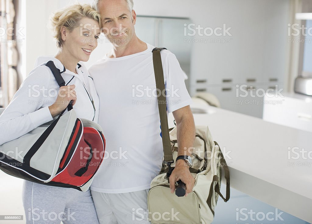 Couple carrying exercise bags royalty-free stock photo