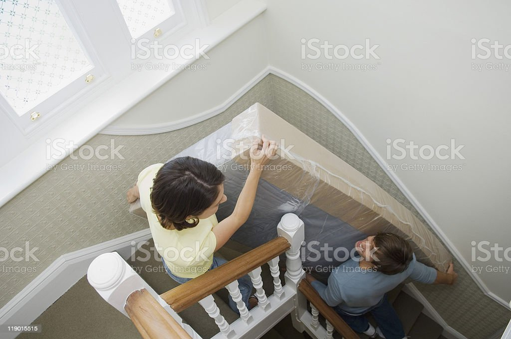 Couple carrying mattress upstairs​​​ foto