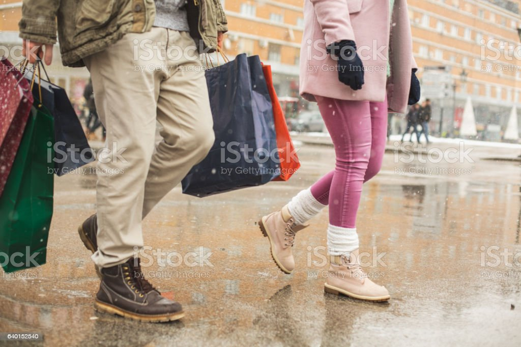 Couple carrying shopping bags in street stock photo