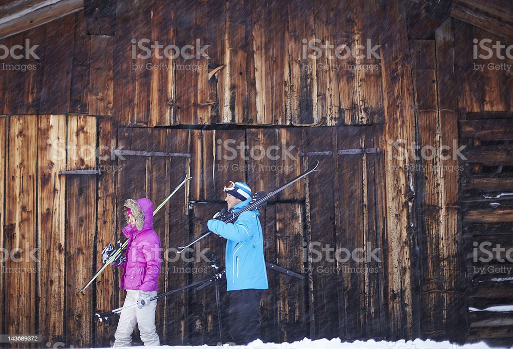 Couple carrying skis and poles in snow stock photo