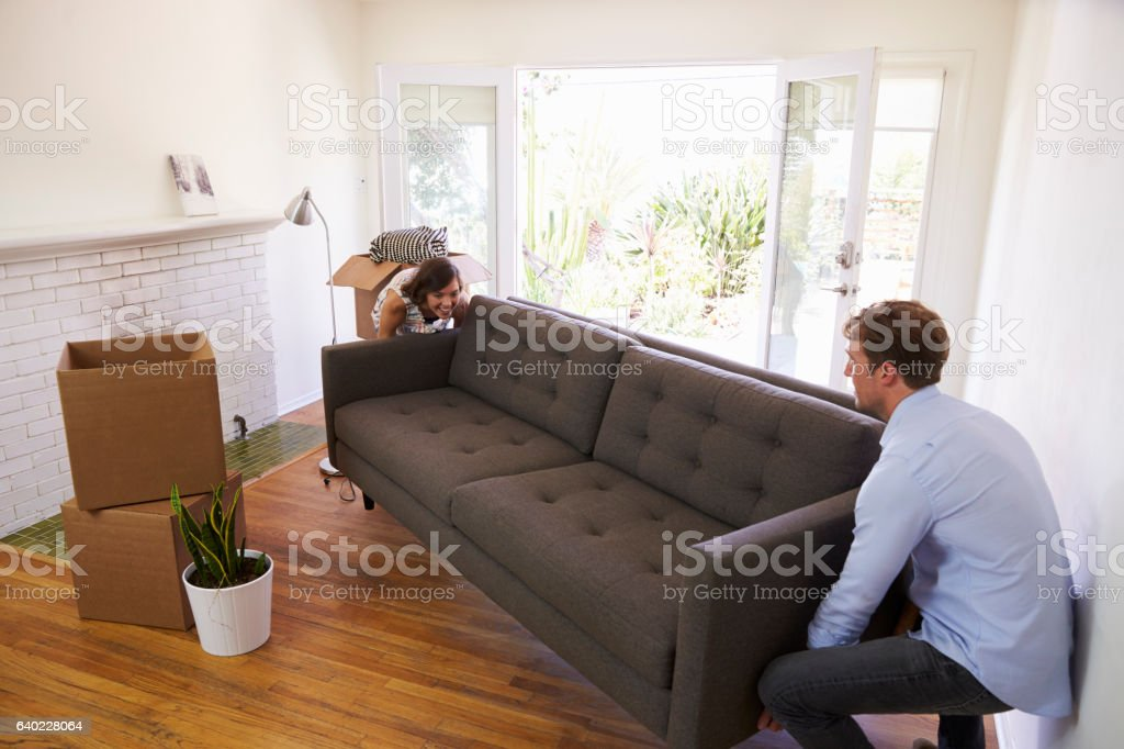 Couple Carrying Sofa Into New Home On Moving Day stock photo
