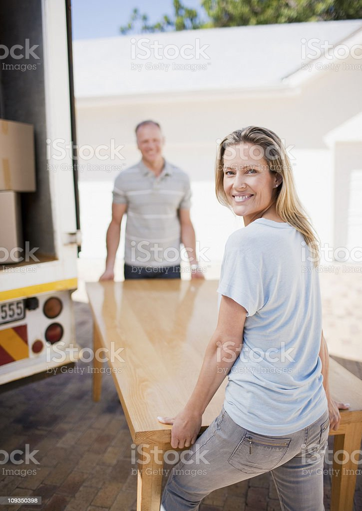 Couple carrying table from moving van royalty-free stock photo