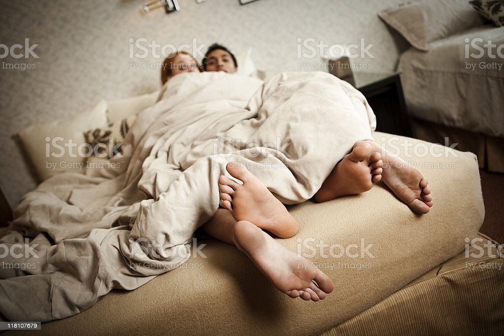 Couple caught in bed with feet hanging out the covers royalty-free stock photo