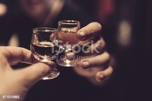 istock Couple celebrating and cheering on good news after a meal, with each a snifter of almond liqueur in their hands. 671014884