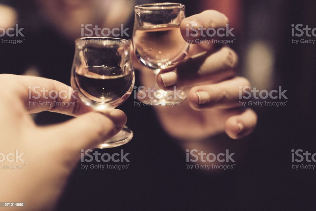 Couple celebrating and cheering on good news after a meal, with each a snifter of almond liqueur in their hands. stock photo