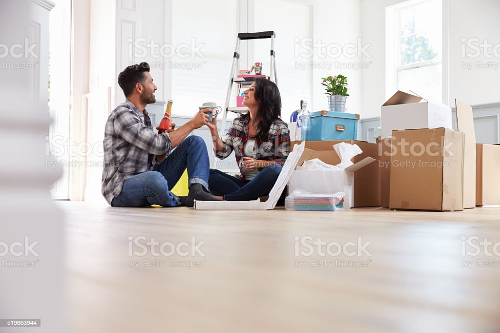 Couple Celebrating Moving Into New Home With Champagne stock photo