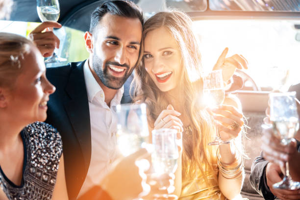 couple celebrating party in limousine with friends - limousine service stock photos and pictures