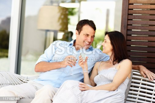 Happy mature couple toasting Champagne while sitting on sofa