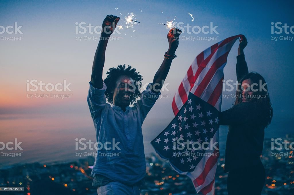 Couple celebrating with sparkler and USA flag at night stock photo