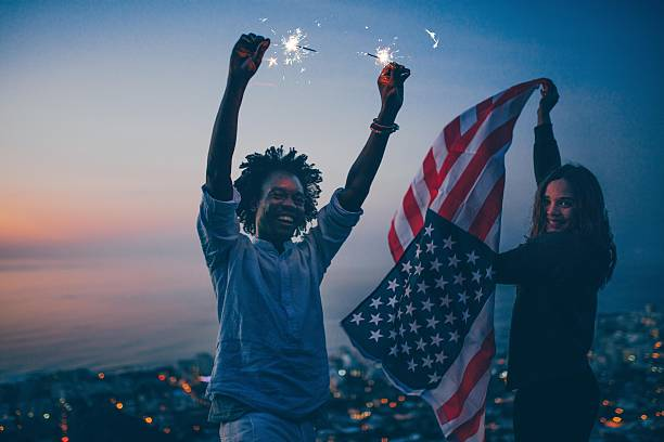 couple celebrating with sparkler and usa flag at night - happy 4th of july 뉴스 사진 이미지