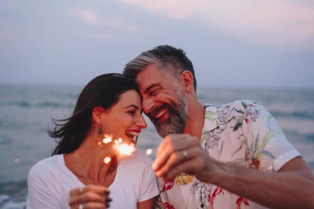 paar vieren met wonderkaarsen op het strand - ouder volwassenen koppel stockfoto's en -beelden