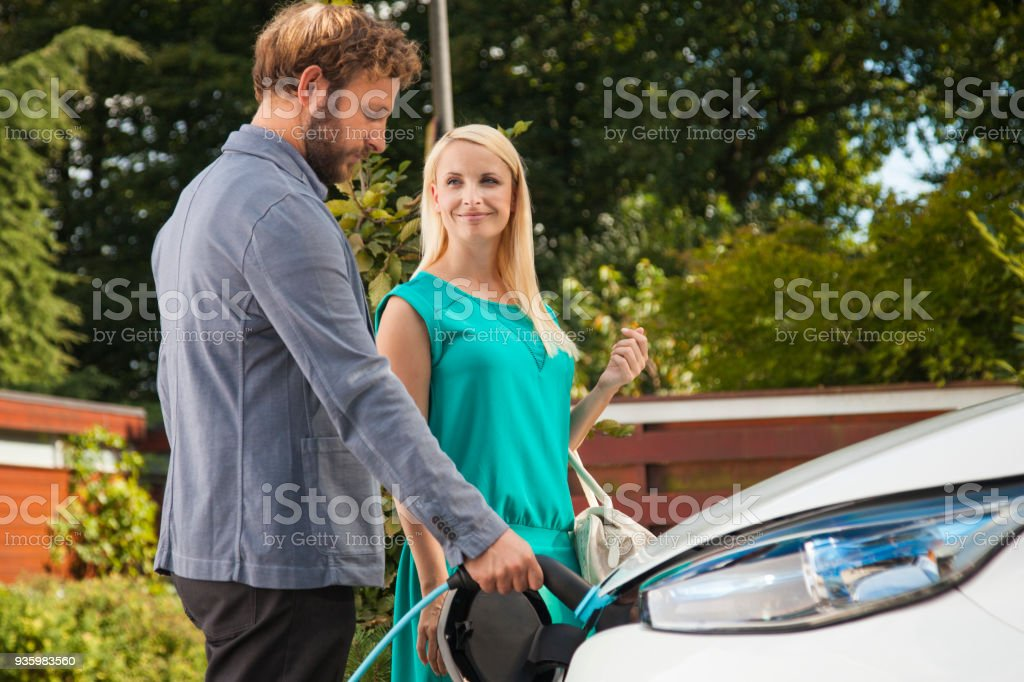 Couple charging the car before going to work stock photo