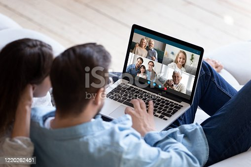 Rear back view married couple resting and chatting with relatives via videoconference videocall application, laptop screen view over spouse shoulder. Distant virtual communication, modern tech concept