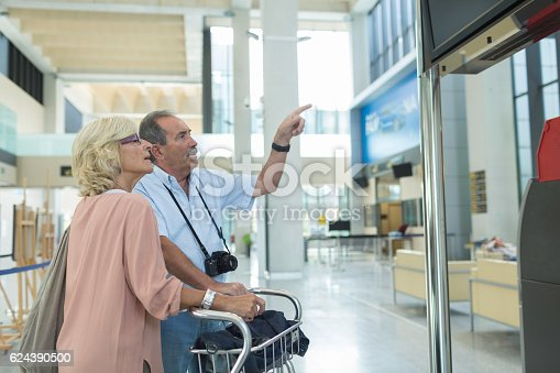 Couple checking for plane delay on departure panel