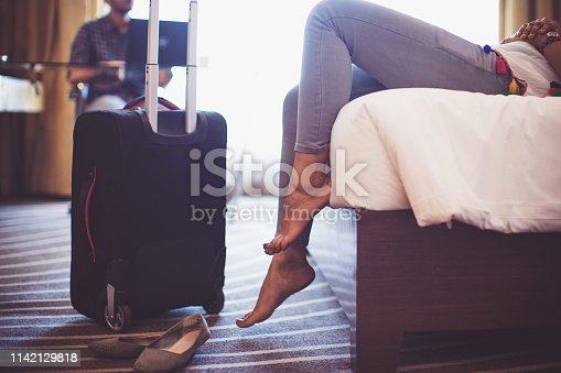 Business Travel, Exhausted, Relaxation - Girl Lying Down the Bed after a long travel while her parter working a laptop at the desk