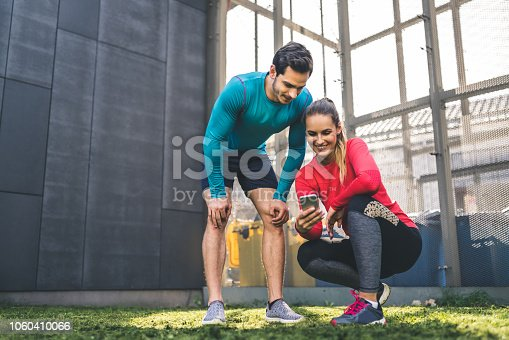 Young man and woman checking fitness progress on smart phone app outdoors. Couple looking at their workout performance on mobile phone.