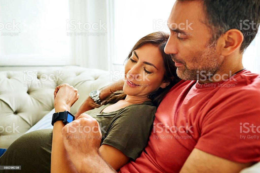 Couple checking condition of pregnancy in smartwatch royaltyfri bildbanksbilder