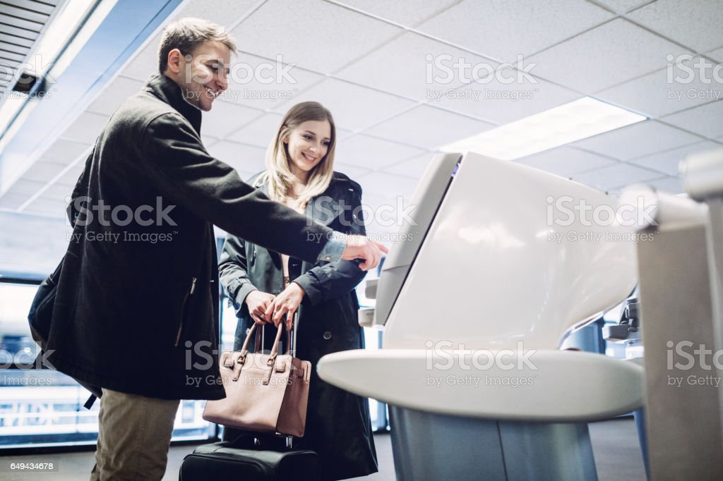 Couple Checking In at Airport Terminal stock photo