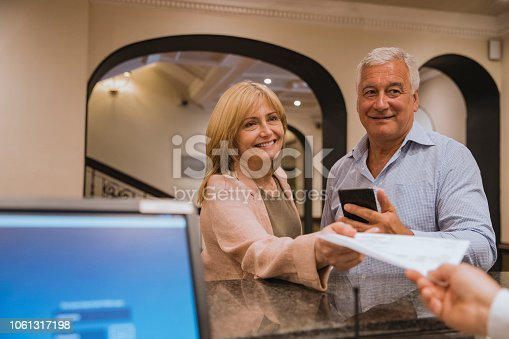 Point of view shot of a mature couple checking in at a hotel reception, they are handing over their tickets.