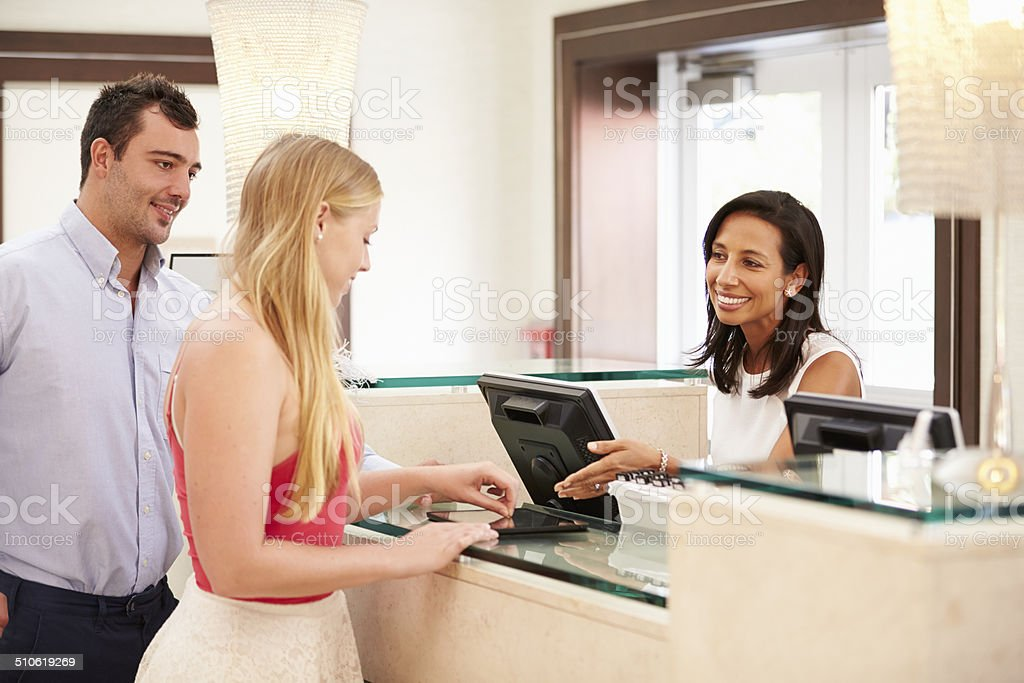 Couple Checking In At Hotel Reception Using Digital Tablet stock photo