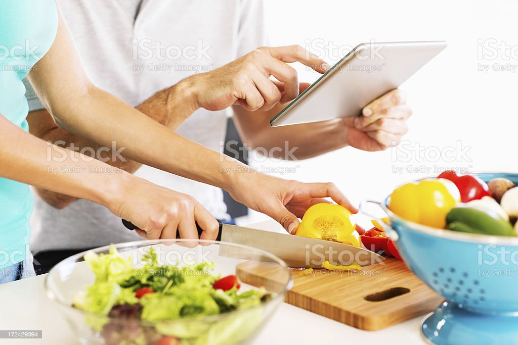 Couple Checking Out Recipe From Tablet Computer royalty-free stock photo
