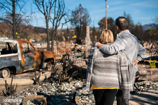 Man and his wife owners, checking burned and ruined house and yard after fire, consequences of fire disaster accident. Ruins after fire disaster.