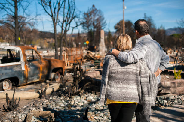 Couple checking ruins after fire disaster. Man and his wife owners, checking burned and ruined house and yard after fire, consequences of fire disaster accident. Ruins after fire disaster. accidents and disasters stock pictures, royalty-free photos & images