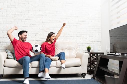 Cheerful Hispanic boyfriend and girlfriend watching soccer match on TV at home