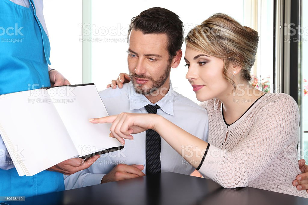couple chooses from the menu stock photo