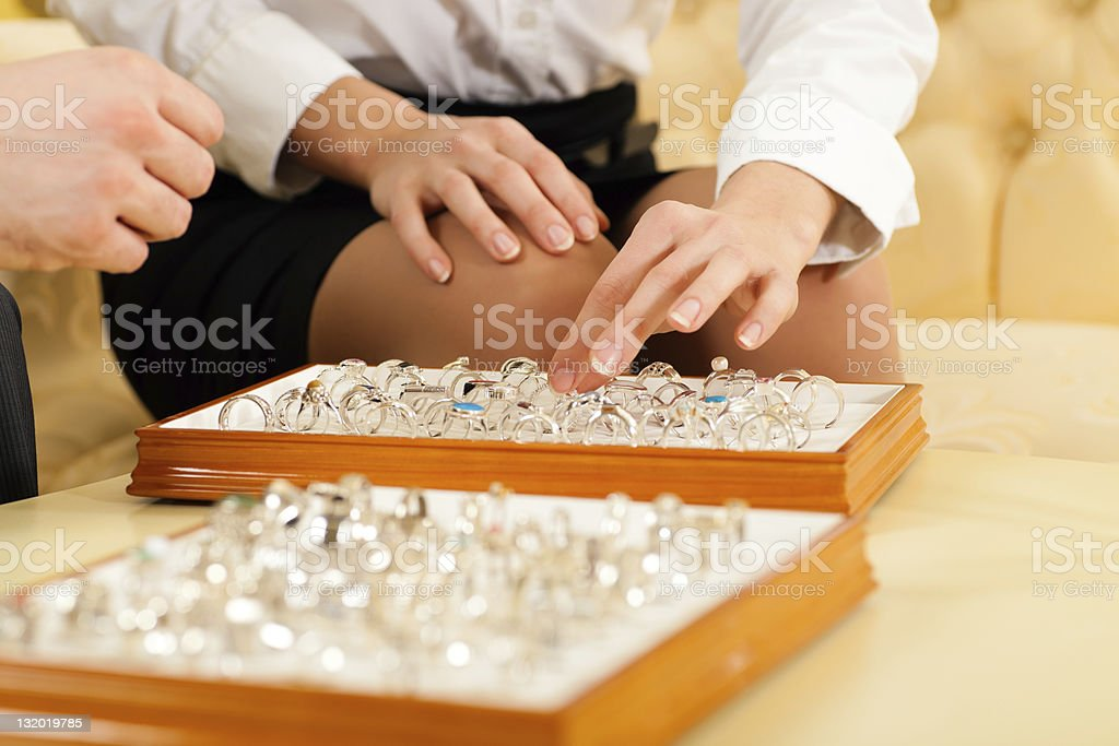 Couple choosing a ring at the jeweller stock photo
