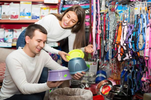 Couple choisissant bol de magasin pour animaux de compagnie - Photo