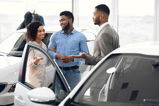 Buying Vehicle. African Family Couple Choosing Car Consulting With Professional Auto Salesman In Dealership Center. Selective Focus