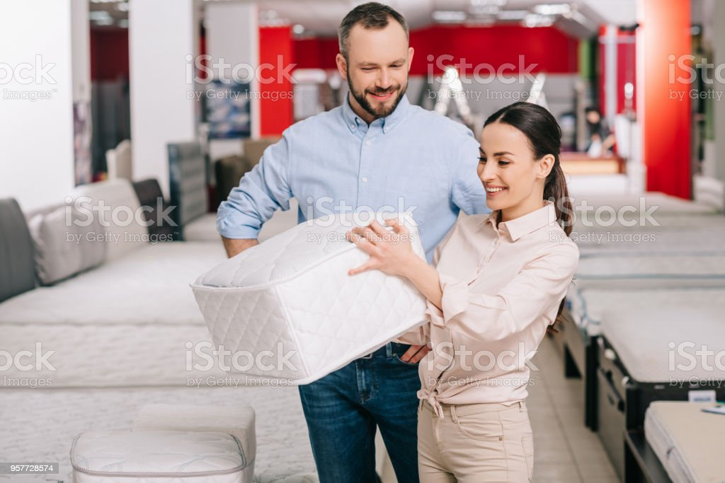 couple choosing folding mattress together in furniture store with...
