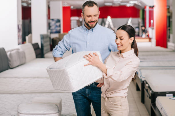couple choosing folding mattress together in furniture store with arranged mattresses - furniture shopping stock photos and pictures