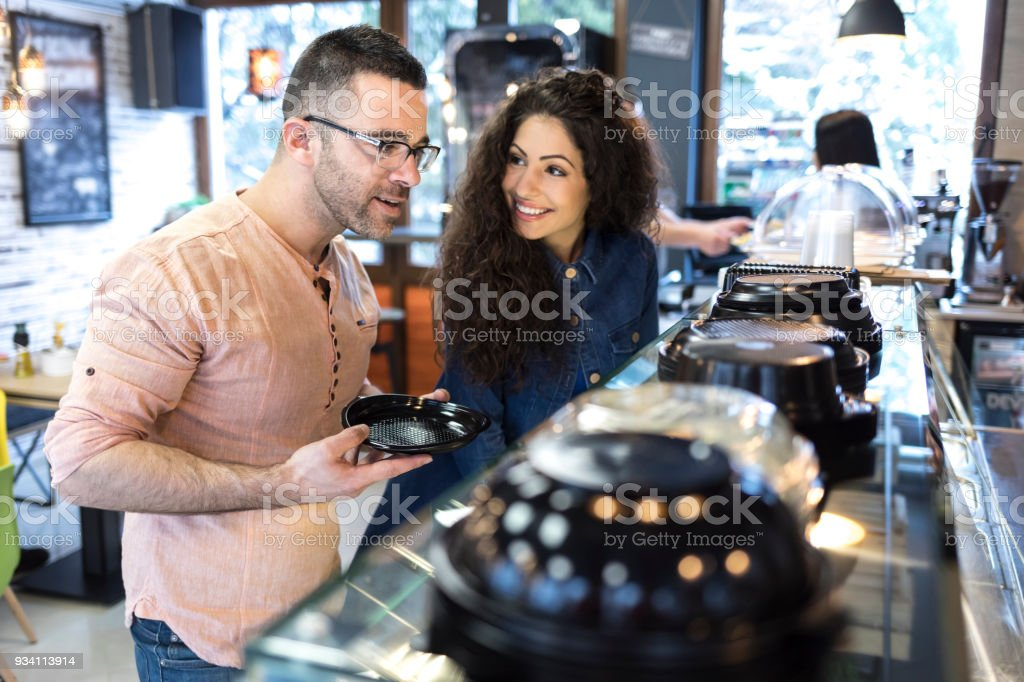Man and woman standing in front of showcase, choosing food.