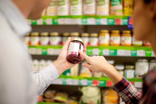 Couple choosing jar of jam Couple choosing jar of marmalade, reading nutrition label label stock pictures, royalty-free photos & images