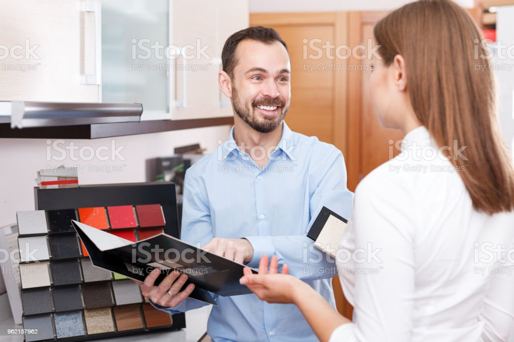 Couple choosing kitchen furniture materials stock photo