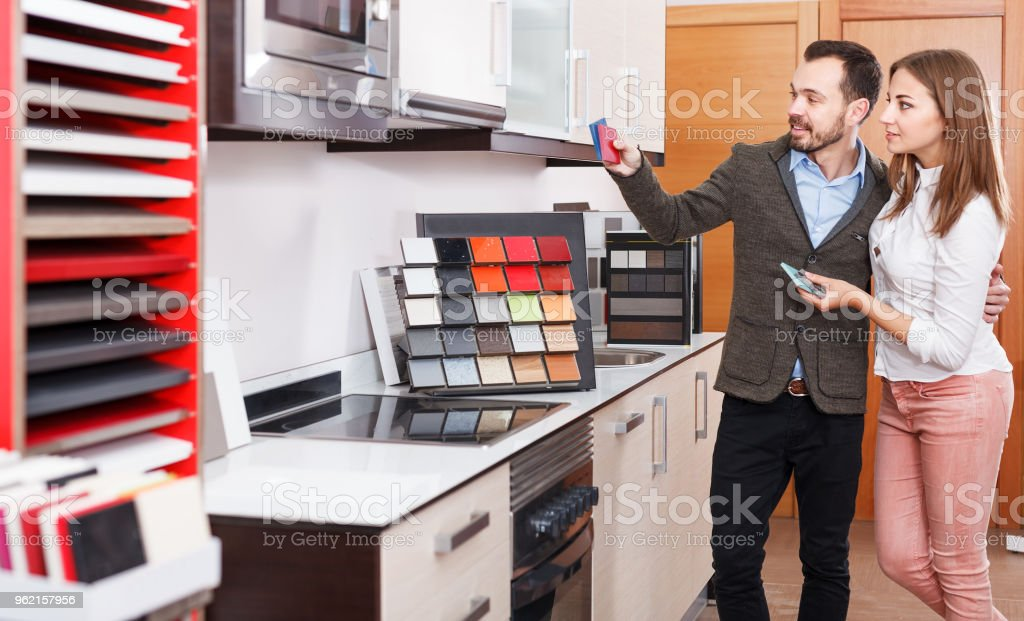 Couple choosing materials for kitchen furnishing stock photo