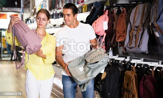 Portrait of young couple choosing new backpack at store