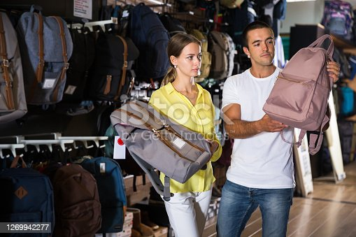 Portrait of young couple choosing new backpack at shop. Focus on woman