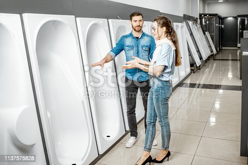 istock Couple choosing new bathtub in the shop 1137575828