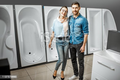 istock Couple choosing new bathtub in the shop 1137575885